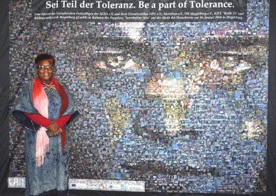 14.Juliana Gombe vor einem aus vielen einhundert Fotos zusammengestellten Mosaik zum Thema Toleranz
